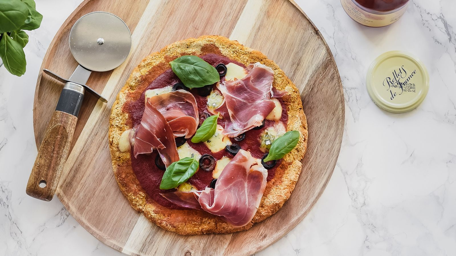Bezglutenowa pizza na marchewkowym spodzie z szynką serrano, serem pleśniowym i oliwkami