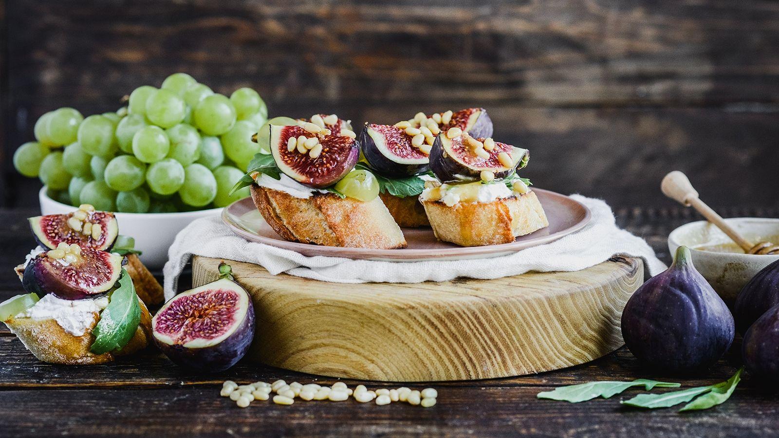 Crostini z kozim serem, winogronami i figami, posypane orzeszkami pinii