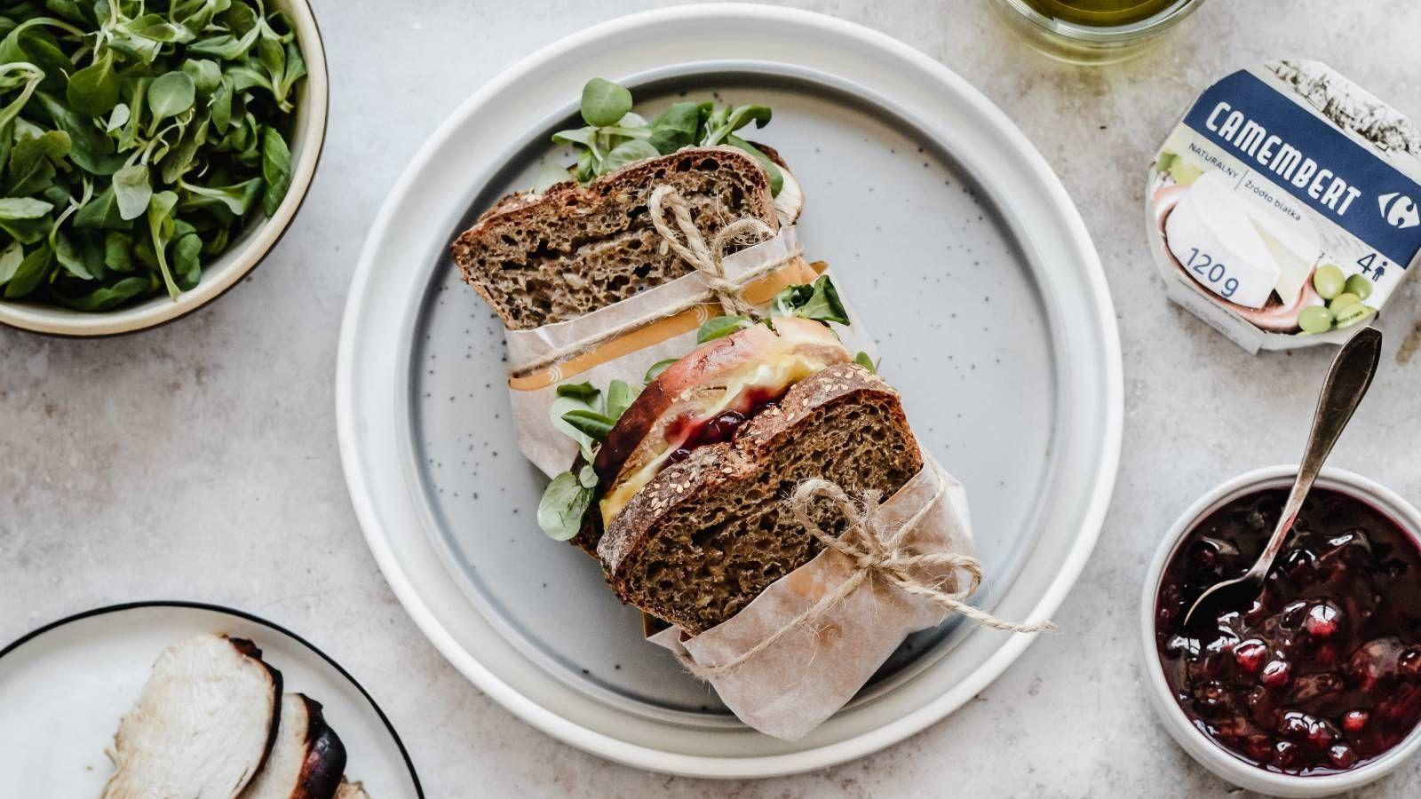 Grillowana kanapka z pieczoną piersią z indyka, camembertem, żurawiną i roszponką
